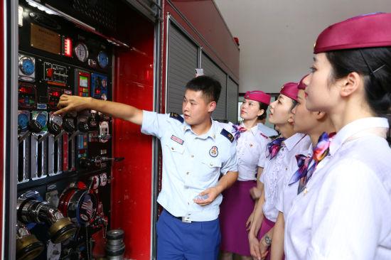 图为消防员正在为乘务员介绍消防器材的使用。真人网上赌钱火车站供图