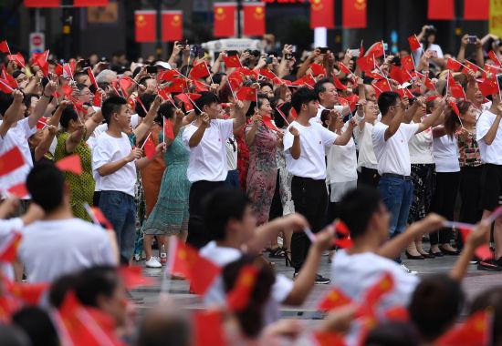 图为众多民众手举五星红旗在解放碑下合唱《我和我的祖国》。陈超 摄