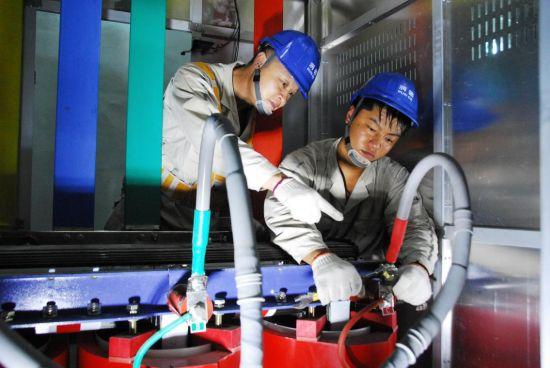 国网重庆合川供电公司员工在配电室内为灯饰工程安装变压器。电力公司供图