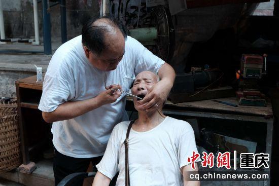 路边牙医摊摊主正在为老人修牙补牙