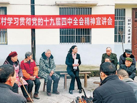 刘后文(中)为村民宣讲党的十九届四中全会精神。记者 颜安 摄