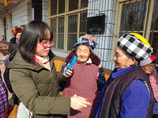 图为拔山镇社保所工作人员上门为行动不便的老人验证登记。