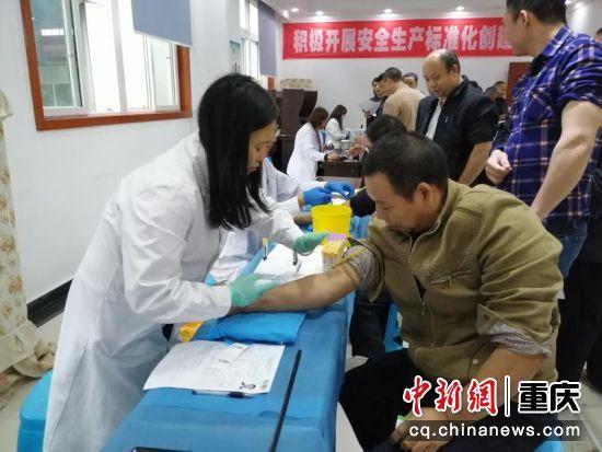 12月11日,工作人员正在为工人采取血样