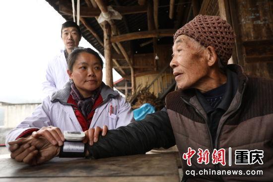 三义乡医务人员正在为老人测量血压。彭水日报供图