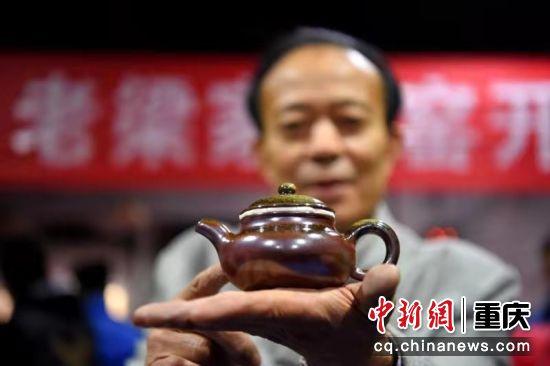 12月28日,陶器烧制技艺(荣昌陶器制作技艺)传承人梁先才正在展示他的作品。