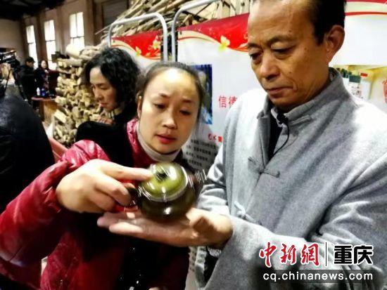 梁先才正在同女儿一道在观看刚出窑的茶壶