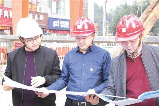黎琦(中)与同事一道研究轨道交通站后工程图纸