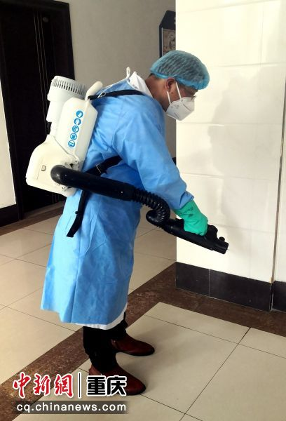 江津区疾控中心消杀工作队工作人员正在进行小区楼道防疫消杀
