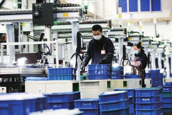 图为在北碚某齿轮公司自动化生产线,员工间隔一定距离操作设备。秦廷富 摄