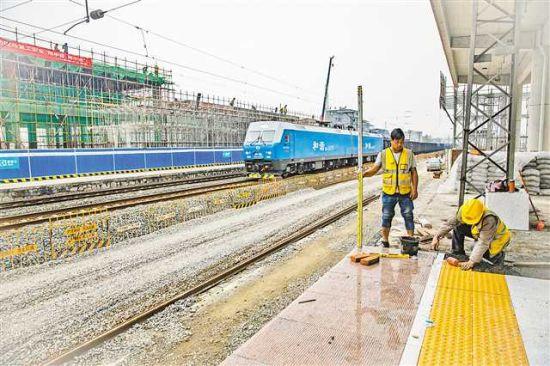 三月二十四日,渝怀铁路酉阳火车站施工现场,工人正在焊接楼层钢筋、铺设站台地板砖。通讯员 黄德权 摄
