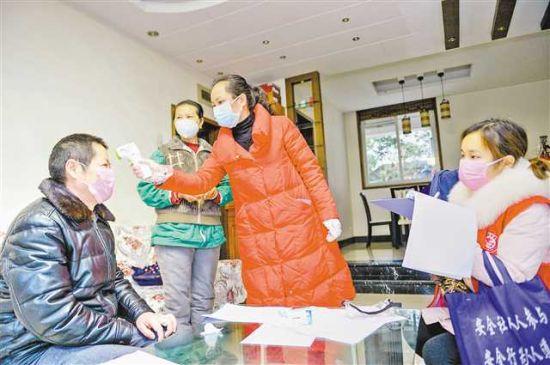 2月2日,在两江新区人和街道邢家桥社区,社区党委书记谢兰(右二)和网格员李丽娟上门为居民测体温,同时拉家常为他们排解焦虑。