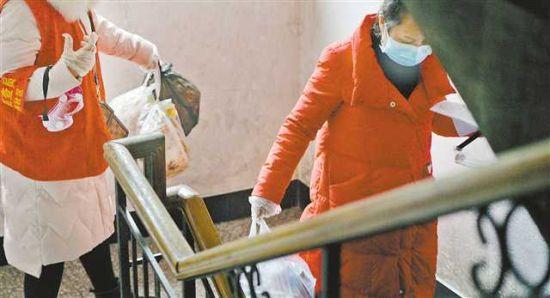 2月2日,在两江新区人和街道邢家桥社区,社区工作人员在排查中顺便把居民的垃圾带下楼,让居民尽量少出门。本组图片均由记者张锦辉摄