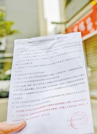 1月24日,在两江新区人和街道,社区工作人员正在挨家挨户张贴自制的《致社区居民的一封公开信》,进行防疫宣传。