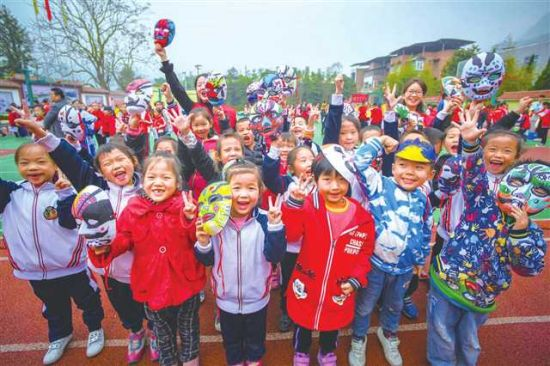 永新镇三会学校,学生展示在志愿者老师指导下绘制的脸谱 摄/陈星宇