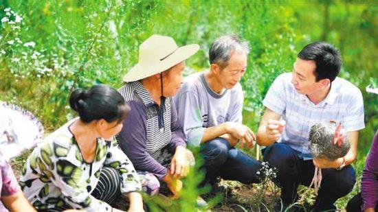 白新亮(右一)与村民交流芦花鸡养殖经验。(受访者供图)