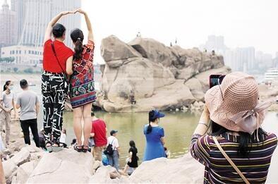 """乱石嶙峋的河滩和石梁上人头攒动,挤满了前来一睹""""神龟""""风采的人潮。 李化 摄"""