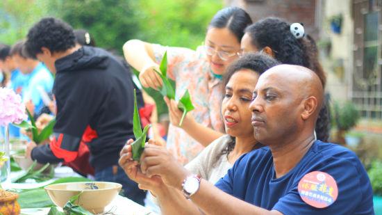 图为外国友人学习包粽子。主办方供图