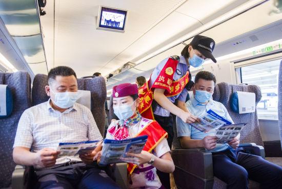 图为志愿者正在列车车厢内为旅客讲解爱路护路知识。铁路公安供图
