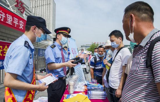 图为重庆北站铁路志愿者为旅客讲解自身安全防范知识。铁路公安供图