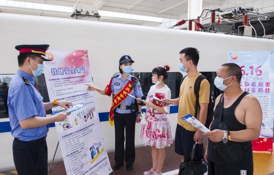 图为重庆北站志愿者正在为旅客讲解爱路护路知识。铁路公安供图