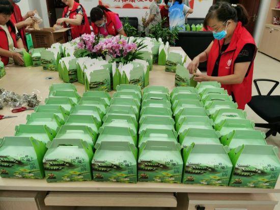 图为志愿者为社区空巢独居老人准备端午节粽子礼包。受访者供图
