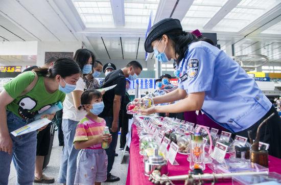 图为民警向旅客讲解如何识别新型毒品。通讯员 胡勇 摄