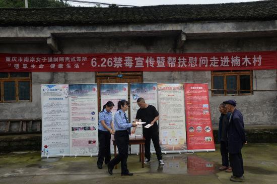 图为民警在村里开展禁毒宣传。重庆市南岸女子强制隔离戒毒所供图