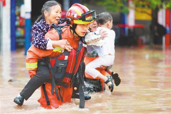 六月二十八日,受暴雨影响,涪陵区龙潭镇龙潭河水位急剧上涨,沿线及场镇大面积被淹。图为消防救援人员正在疏散被困群众。通讯员 肖乐峰 摄