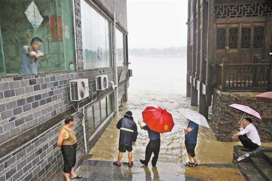 6月28日,黔江区濯水古镇干部群众在观察洪水的涨势。(本组图片均由特约通讯员杨敏摄)