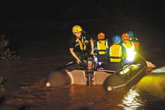 6月27日晚,消防员在黔江区冯家街道桂花社区沿溪沟水面上救援。