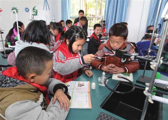 鸣玉镇逸夫村小学生在设备齐全的实验室进行试验。 摄/喻梵