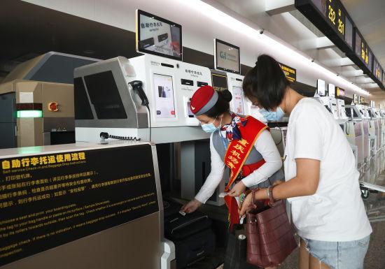 图为旅客正在工作人员引导下使用自助行李托运设备。通讯员 莫晓健 摄