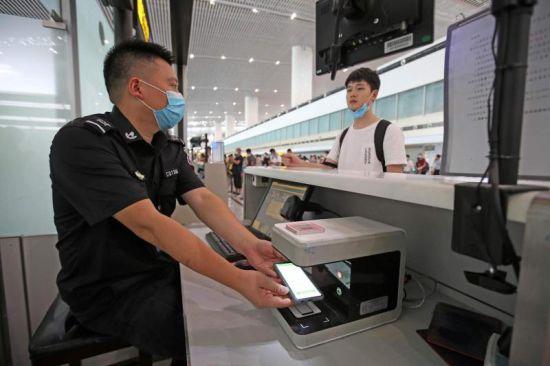 图为乘客使用登机牌和身份证合二为一的二维码通过安检验证。通讯员 莫晓健 摄
