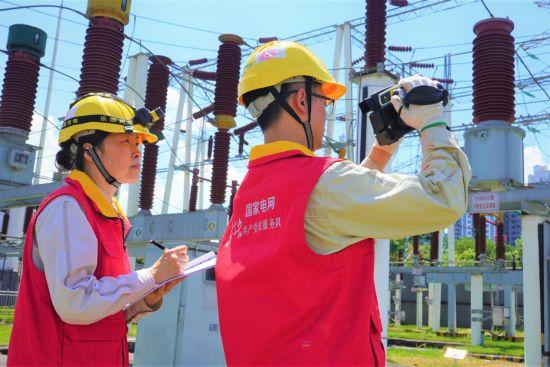 国家电网(丰都运检)红岩共产党员服务队人员用红外线测温仪对变电站设备进行温度监测、记录,确保电网安全运行。
