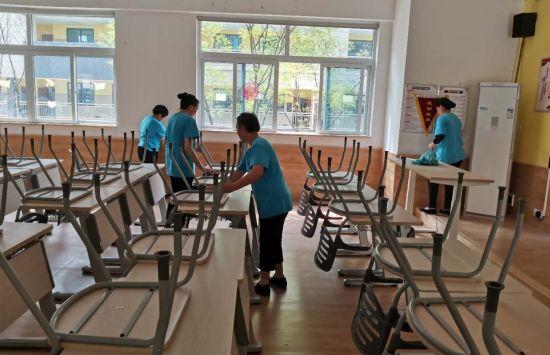 图为保洁人员在教室内整理学生课桌椅。李俨 摄
