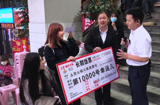 """图为火锅店向国庆期间累计排队的第10000号客人发放""""长期饭票""""。杨新宇 摄"""