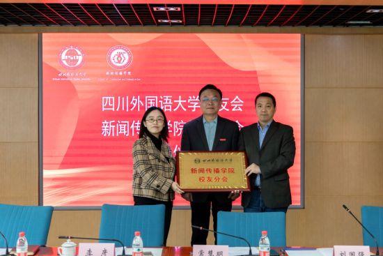 图为四川外国语大学副校长李彦为新闻传播学院校友分会颁发铭牌。主办方供图