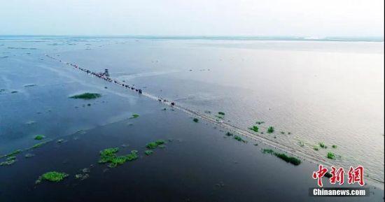 从航拍画面中,汽车排成长龙,在水中行驶,划出一道水线。 鲍赣生 摄