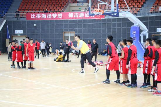 图为篮球专业队运动员、教练员为青少年选手传授篮球知识。向霞蔚 摄