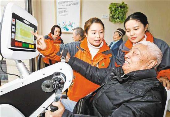 """图为12月8日,万盛经开区万盛街道安博馨社区""""智慧养老""""服务站,服务人员正指导老人使用智能健身器材。"""