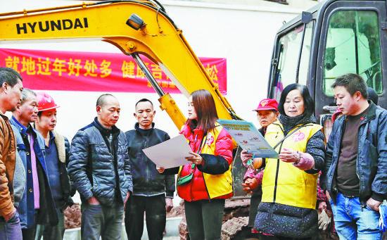 1月26日,沙坪坝区联芳街道一处建筑工地,党员志愿者向工人们宣传就地过年。特约摄影 孙凯芳/视觉重庆