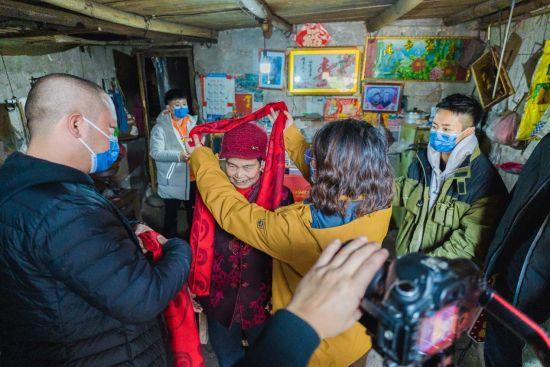 图为重庆鹏龙奔驰爱心车队为新民村老人带上喜庆的红围脖。主办方供图