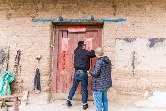 图为重庆鹏龙奔驰爱心车队为新民村老人家里贴春联。主办方供图