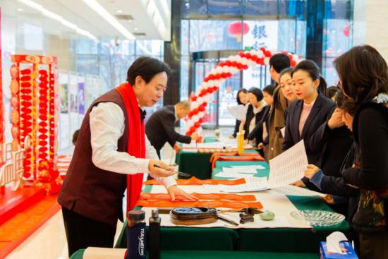 图为杨建明正在为客户写春联。中信银行重庆分行 供图