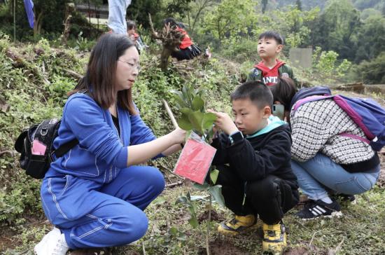 图为夏红丽和儿子正在给刚种下的树苗留言。