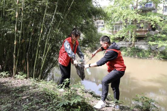 """图为""""河小青""""沿着长江二级支流鸭溪河拾捡垃圾。"""