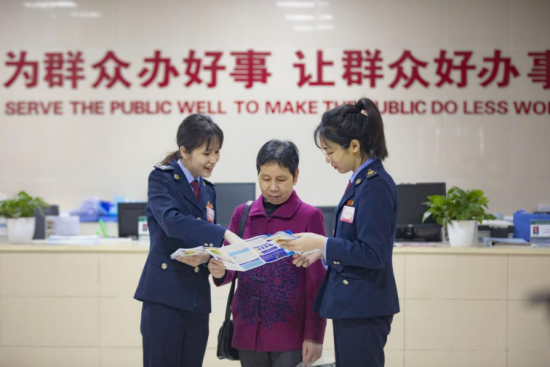 """""""党员春风服务队""""在社区便民服务中心为纳税人解答涉税问题。 姜钟伟 摄"""