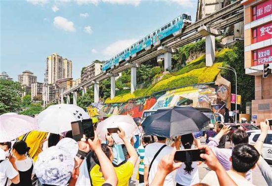 """②5月2日,渝中区李子坝,众多外地游客在""""轻轨穿楼""""景点前拍照。记者 崔力 摄/视觉重庆"""