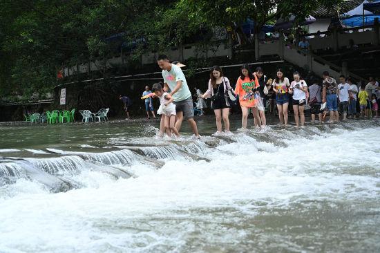图为游客正在玩水消暑。陈超 摄