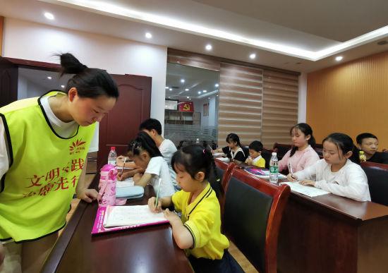 图为志愿者为暑期爱心托管班学生进行辅导。羽裳路社区供图
